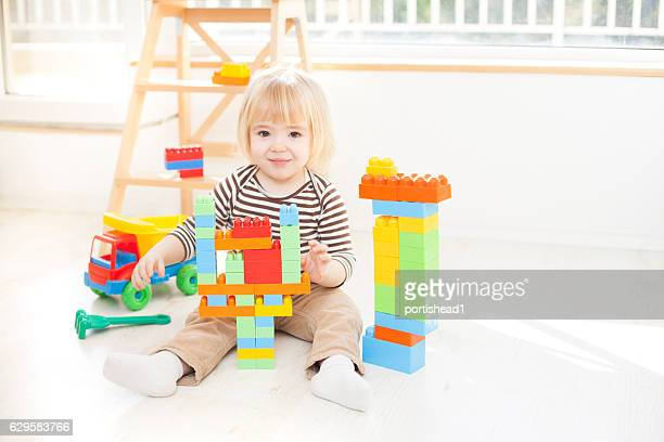 Little boy playing with colorful plastic blocks