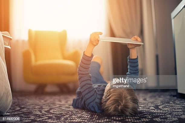 Kleine Jungen spielen mit Digitaltablett auf dem Boden