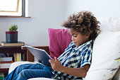 Little african boy sitting on sofa and playing game on digital tablet. Portrait of a young black child at home watching cartoon on the laptop. Modern kid and education technology.