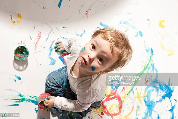 Little boy playing with finger paint
