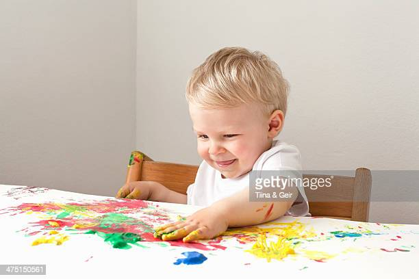 Little boy playing with finger paints