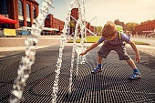 Hot summer day in the city. Little boy is having fun playing in the city fountain after school. He is reaching and touching the water.