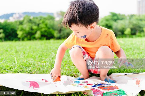 Little boy playing with hand painting.