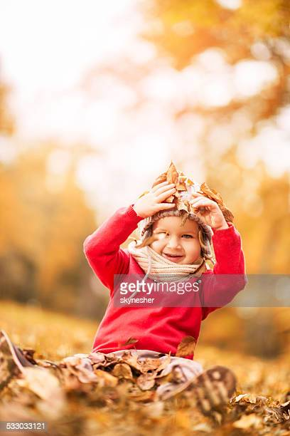 Little boy playing with leaves.