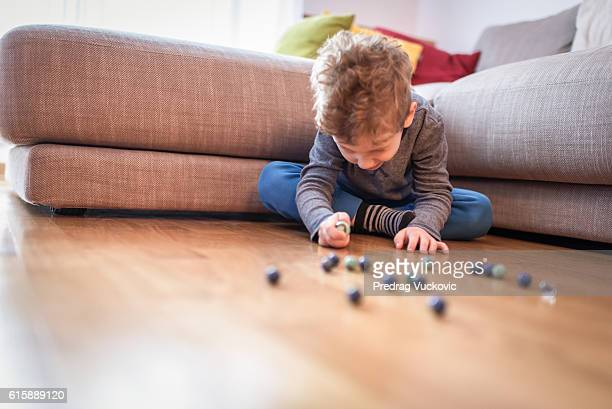 Little boy playing with marbles