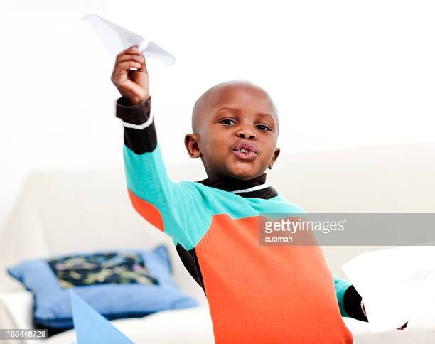 Little boy playing with paper airplane