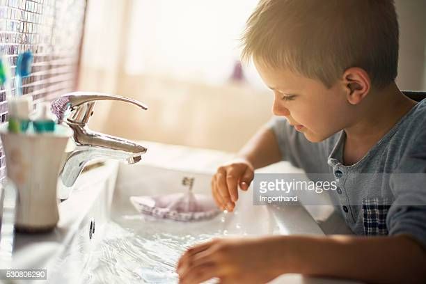 Little boy playing with paper boat in sink