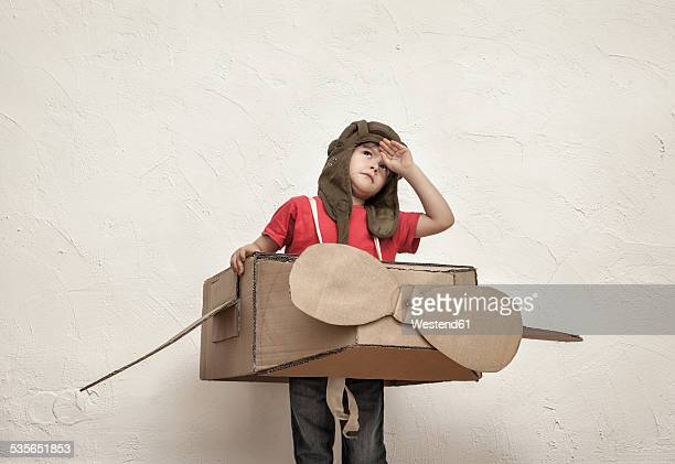 Little boy playing with pilot hat and cardboard box aeroplane