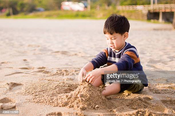 Little boy playing with sand at the beach.