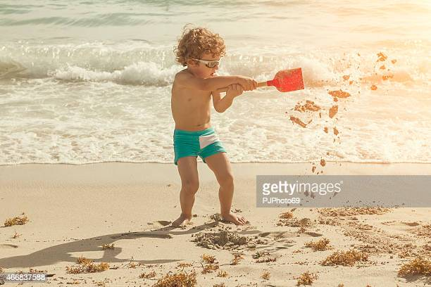 A little boy playing with sand on the beach