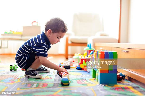 Little boy playing with small cars at home