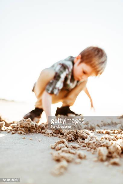 little boy playing with the sand on the beach