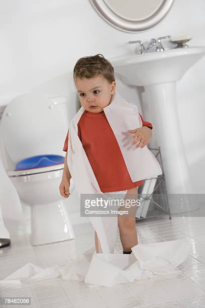 Little boy playing with toilet paper in bathroom