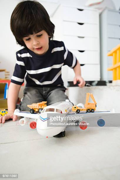 Little boy playing with toy airplane and toy trucks