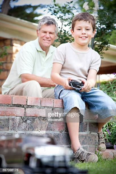 Little boy playing with toy car while his grandfather watching in the background