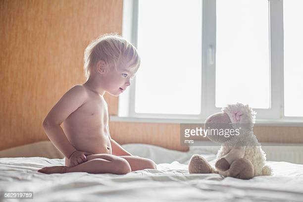 Little boy playing with toy sheep