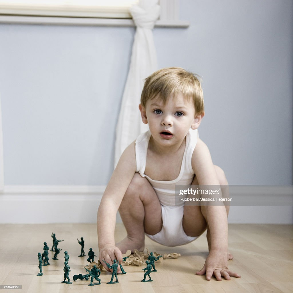 little boy playing with toy soldiers : Stock Photo
