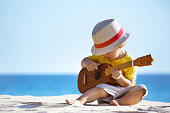 Little boy plays on Hawaiian guitar or ukulele at sea beach background. Space for text