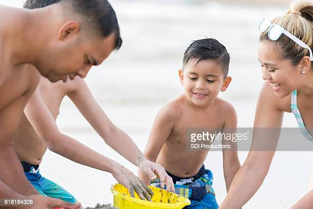 Little boy plays in the sand with his family