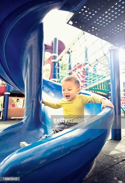 Little boy plays slide happily