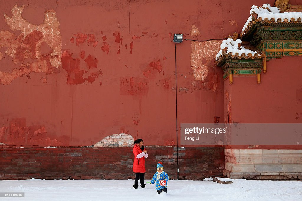 A little boy plays with his mother at the Imperial Ancestral Temple following overnight snowfall on March 20, 2013 in Beijing, China. Beijing witnessed a heavy spring snowfall with a depth reaching 10-17 centimeters overnight.