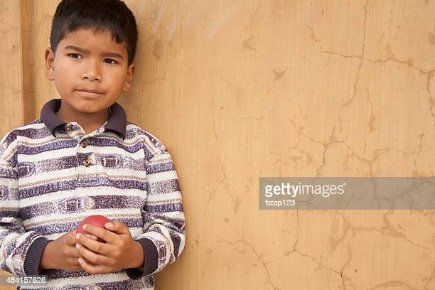 Little boy plays with small ball in India city streets.