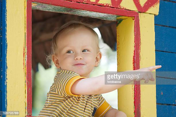 Little boy pointing from the window