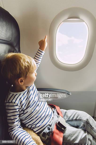 Little boy pointing out of an airplane window