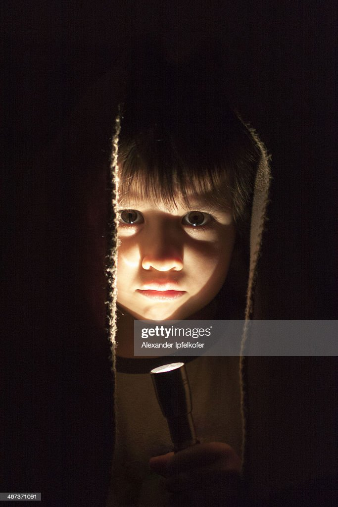 Little boy portrait lit by torchlight : Stock Photo