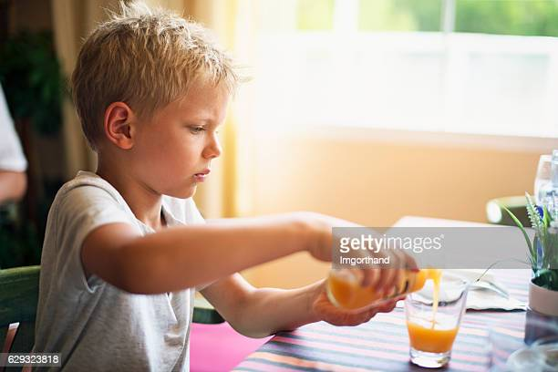 Little boy pouring a glass of orange juice