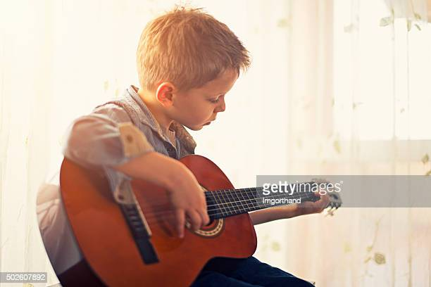 Little boy practicing guitar.