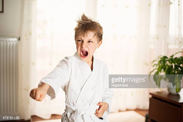 Little boy practicing karate at home