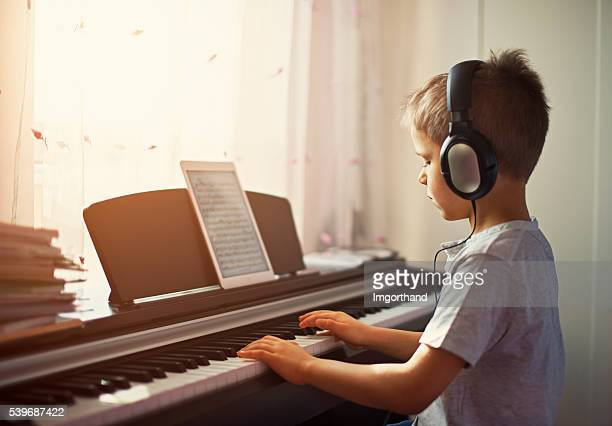Little boy practicing modern digital piano.