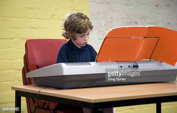 Little boy practicing on an electronic keyboard
