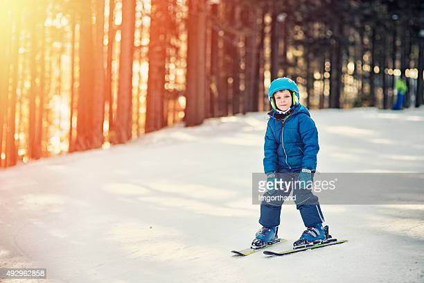 Little boy practicing skiing on ski lesson