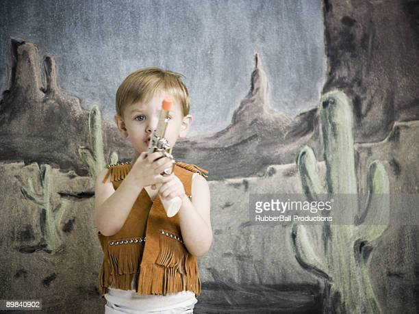 little boy pretending to be cowboy
