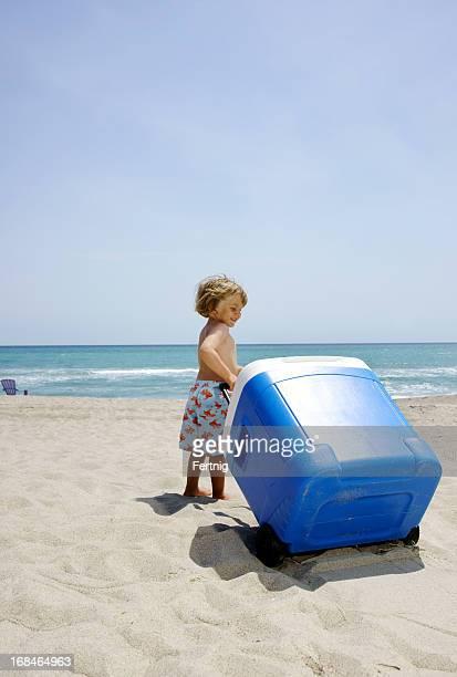 Little boy pulling a big cooler onto the beach