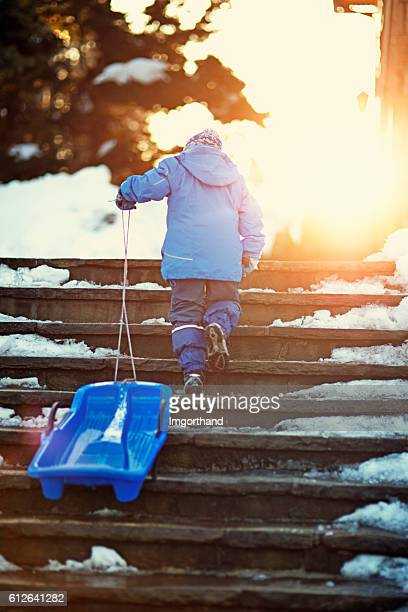 Little boy pulling sled on stairs, returning home from sledding.