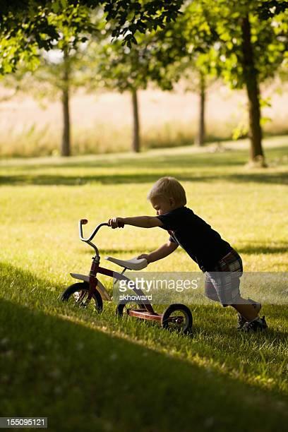 Kleine Jungen Schieben Dreirad bergauf