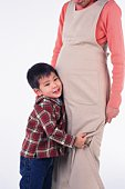 Little Boy putting his ear on the stomach of his pregnant mother, Smiling, Side View
