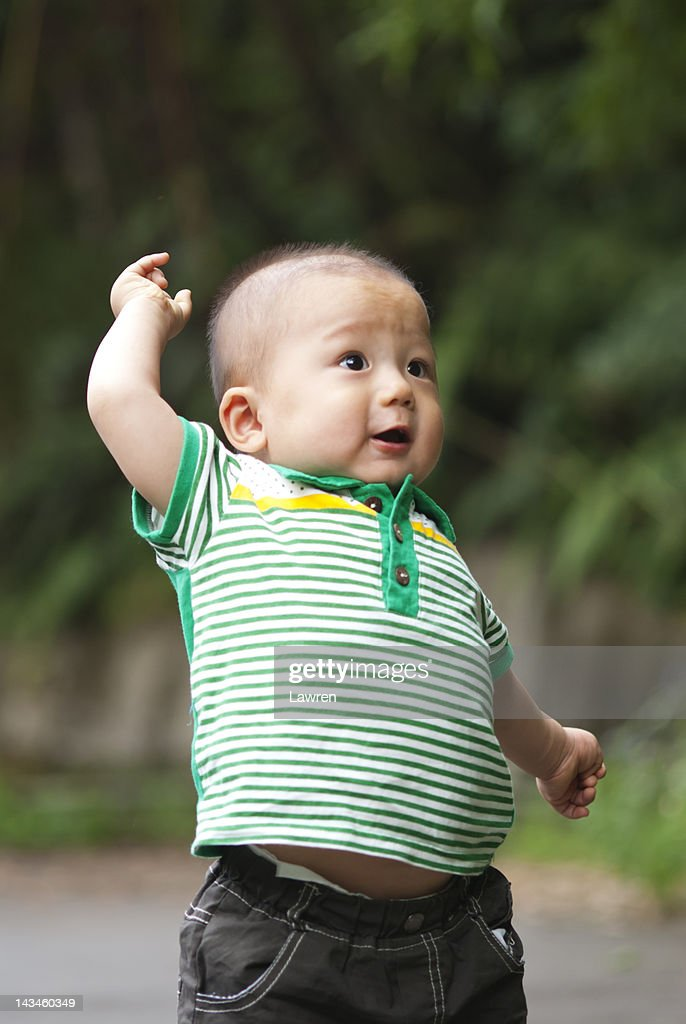 Little boy raises his hand : Stock Photo