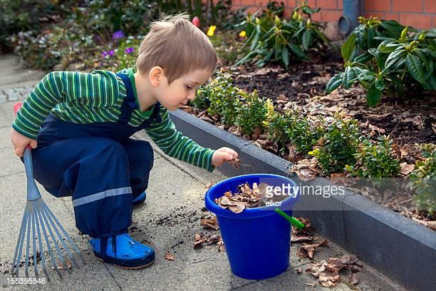 Kleine Junge Raking Blätter im Frühling Garten