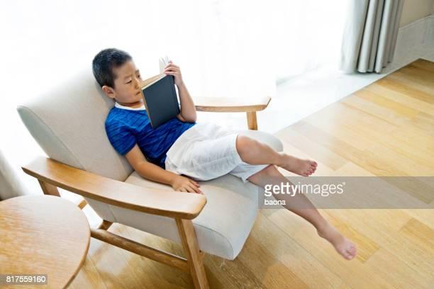 Little boy reading a book in armchair