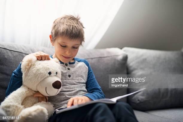 Little boy reading a book to his teddy bear