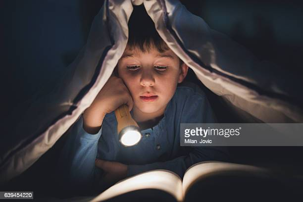 Little boy reading a book under the covers with flashlight