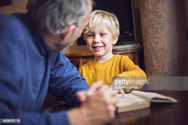 Little boy reading a book with his Grandpa