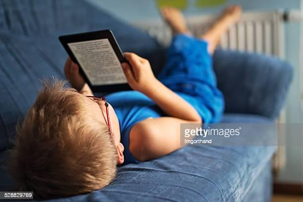 Little boy reading un sofá, libro electrónico en
