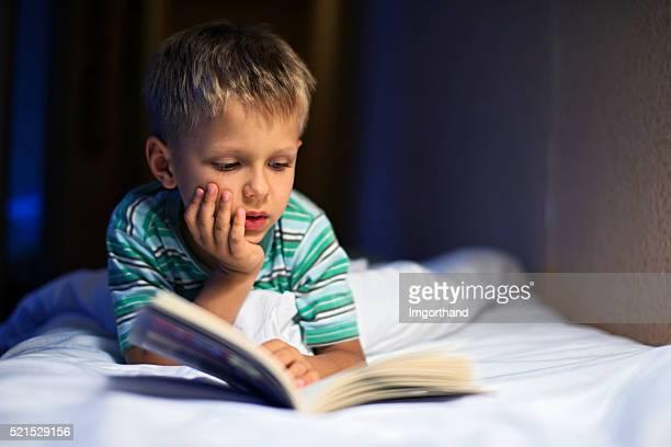 Piccolo ragazzo leggendo un libro a letto