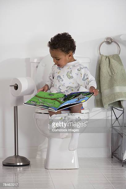 Little boy reading book while on the toilet