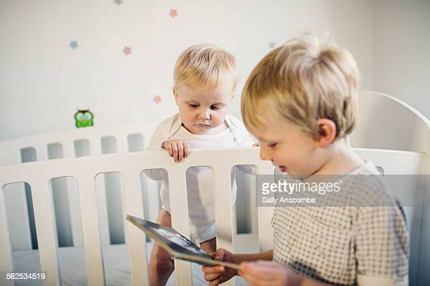 Little boy reading to his baby sister